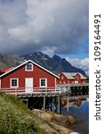 Red fishing huts in town of Henningsvaer on Lofoten islands in Norway - stock photo