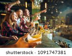 Stock photo splashing beer in the foreground and in focus sport people leisure friendship and entertainment 1091747381