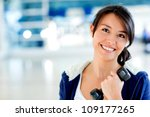 Happy woman at the gym holding a free-weight - stock photo