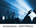 Small photo of Silhouettes of people in a bright in the pop rock concert in front of the stage. Hands with gesture Horns. That rocks. Party in a club