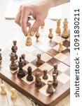 Small photo of close-up partial view of person playing chess at wooden table