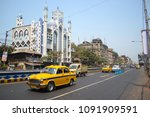 Small photo of Kolkata, India - March, 2014: Classic yellow taxi cab ambassador on the street in a front of mosque in Calcutta. Indian traffic road
