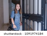 asiatic woman entering her house | Shutterstock . vector #1091974184