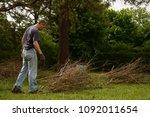man bundling twigs doing yard... | Shutterstock . vector #1092011654