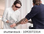 Small photo of Cosmetologist with patient and professional tattoo removal laser in salon
