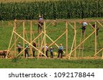 """Small photo of New Providence, PA, USA - July 30, 2013: Amish farmers at a """"barn raising"""" in rural Lancaster County."""