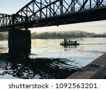 old railway bridge over calm... | Shutterstock . vector #1092563201