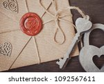Small photo of love letter in a craft envelope with a sealing wax seal in the form of a heart on a wooden background. Free space