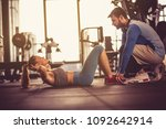 trainer assisting young woman... | Shutterstock . vector #1092642914