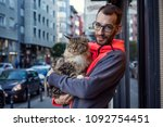 Stock photo handsome young man holding beautiful maine coon cat on the street cat lovers cat loving 1092754451