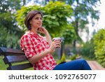 beautiful young woman in park... | Shutterstock . vector #1092765077