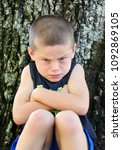 small boy leans against a tree...   Shutterstock . vector #1092869105