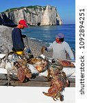 Small photo of FISHERMEN WITH THEIR CATCH OF SHELLFISH. ETRETAT. NORMANDY. FRANCE. JUNE 2014. The iconic cliffs and the Arch Porte d'aval with the local fishermen and their catch of shellfish.