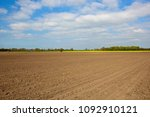 patterned plow soil with yellow ... | Shutterstock . vector #1092910121