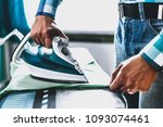 man at home ironing clothes.... | Shutterstock . vector #1093074461