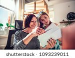 Small photo of Mother and daughter sitting by the window and checking mail together at home office