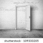 open door in white brick room - stock photo