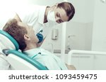 Small photo of Complete attention. Careful concentrated dentist looking into the mouth of her patient while curing him with a help of a dental engine
