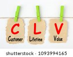 Small photo of Customer Lifetime Value- CLV writen on old torn paper with clip hanging. Acronym business concept.
