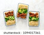 Small photo of Asian style teriyaki sauce chicken meat balls with broccoli and rice prepared and put in a take away lunch boxes, view from above