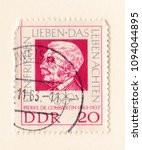 Small photo of Leeds, England - May 19 2018: An old red east german stamp with an image of Baron Pierre de Coubertin founder of the International Olympic Committee