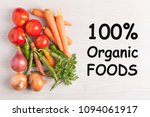 Small photo of 100% Organic Foods written on wooden desk and group vegetables. Top view.