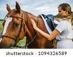 a woman jockey strokes a horse... | Shutterstock . vector #1094326589