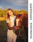 a woman jockey strokes a horse... | Shutterstock . vector #1094326595