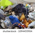 Small photo of broken yellow umbrella and many rags in the junkyard