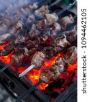 Small photo of Shashlik preparing on a barbecue grill over charcoal. Pieces of meat on skewers. Shish kebab prepare on fire.