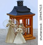 Handmade christmas decoration angels  from straw and lantern with a  candle. Products of mass production. - stock photo