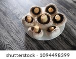 peeled champignons in a plate... | Shutterstock . vector #1094498399