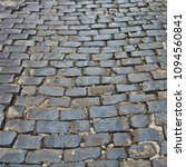 Small photo of Cobblestone road of an ancient town. Beautiful stone pavement. Old roadway. Textured urban background. Eternal city.
