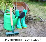 Green garden watering-can rubber knee-boots and rakes. Garden inventory - stock photo