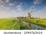 windmill on green meadow by... | Shutterstock . vector #1094762414