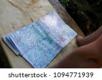 Small photo of Map, road map lies on a wooden table, two arms protrude into the picture