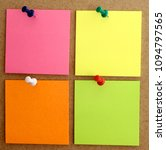 Small photo of square colored paper sheets, pink, green, yellow and orange, nailed to the cork wall with colored thumbtacks. It is used to write notes, messages, incorporate text.