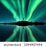 Aurora borealis and silhouette of standing man. Lofoten islands, Norway. Aurora and happy man. Stars and green polar lights. Night landscape with aurora, man, lake, sky reflection in water. Travel - stock photo