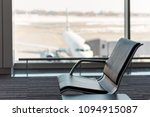 Small photo of The waiting hall in airport terminal, focus on the seats and blurred aircraft behind the window. Vacation concept, beautiful summer travel background