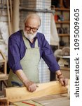 Small photo of senior citizen making wooden bench from planks. creative idea