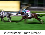 Small photo of Racehorses ridden by jockeys running fast during the race at racetrack. Striving to victory. Hong Kong Happy Valley race course. Motion blur.