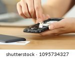 Small photo of Close up of a woman hands putting the sim card on the phone on a table