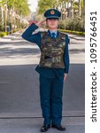 Small photo of Beijing, China - April 29, 2010: Young fierce and proud male airforce officer in blue uniform salutes in front of green tree lane leading to his base. Wears camouflage bullet-proof vest.
