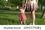 mum walks in park on lawn with... | Shutterstock . vector #1095779381