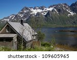 Wooden hut by the fjord surrounded by snowy peaks of mountains on Lofoten islands in Norway - stock photo