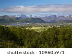 Picturesque panorama on Lofoten from Justadtinden with green lowlands and snowy peaks of mountains - stock photo
