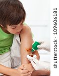 Boy receiving emergency treatment - disinfecting a wounded leg - stock photo
