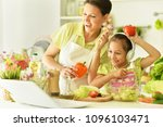 mom teaches daughter to cook | Shutterstock . vector #1096103471