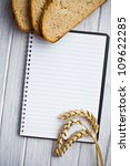 blank notebook with bread and wheat on wooden table - stock photo