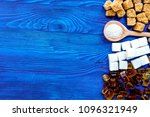 Small photo of lumps and sanding sugar for sweets on blue kitchen table background